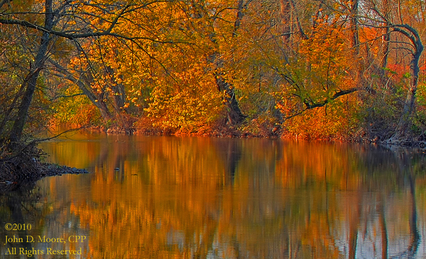 Before the Pennsylvania sun sets, the autumn colors are reflected in the river.